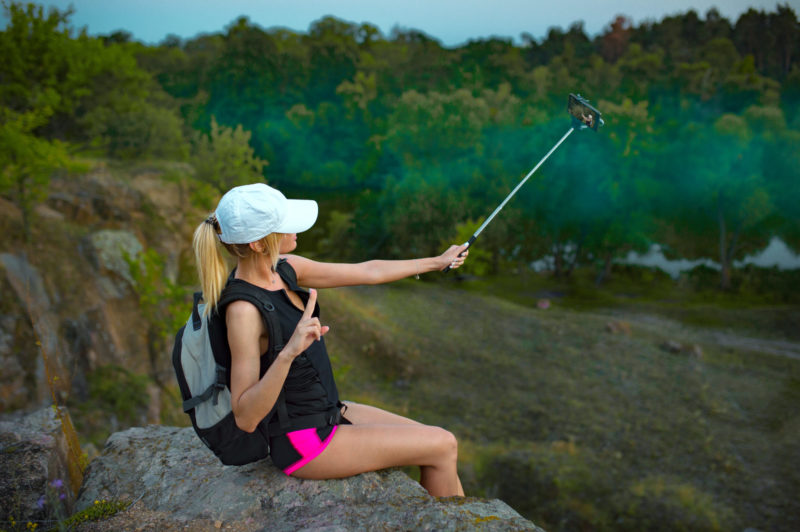Young girl backpacker, sitting on top of the hill, takes selfie with the selfie stick and enjoys the nature. Misty forest background